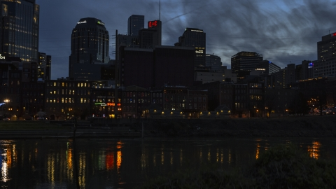 DXP002_120_0020 - Aerial stock photo of Skyscrapers at twilight seen from low over the river, Downtown Nashville, Tennessee