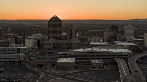 DXP002_122_0009 - Aerial stock photo of Sunset behind office tower and shorter hotel tower, Downtown Albuquerque, New Mexico
