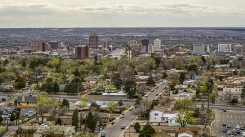 DXP002_126_0005 - Aerial stock photo of Wide view of city's high-rises seen while flying by homes, Downtown Albuquerque, New Mexico