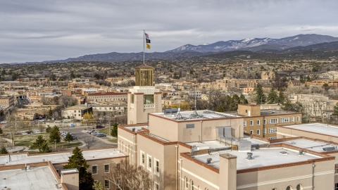 DXP002_131_0008 - Aerial stock photo of The tower and flags on Bataan Memorial Building, Santa Fe, New Mexico