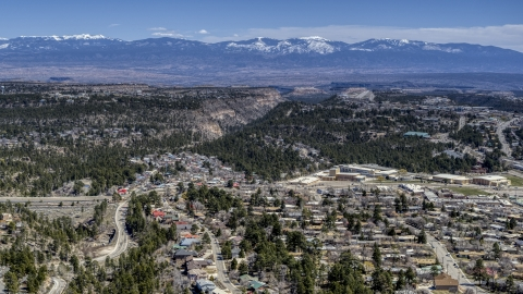 DXP002_134_0002 - Aerial stock photo of Distant mountains seen from neighborhoods near mesas and canyons in Los Alamos, New Mexico