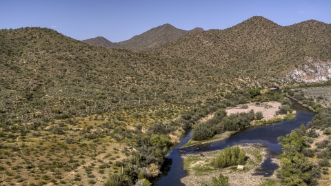 DXP002_141_0024 - Aerial stock photo of A shallow river bordered by desert hills with cactus