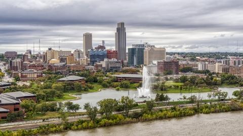 DXP002_169_0009 - Aerial stock photo of The city's skyline while seen from near a park fountain, Downtown Omaha, Nebraska