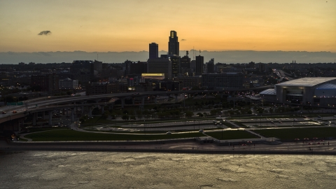 DXP002_172_0015 - Aerial stock photo of A view of the skyline from the river at twilight, Downtown Omaha, Nebraska