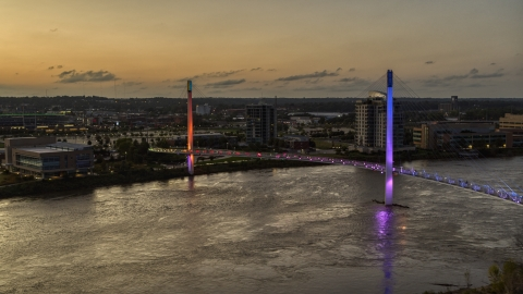 DXP002_172_0017 - Aerial stock photo of A colorful pedestrian bridge spanning the Missouri River at twilight, Omaha, Nebraska