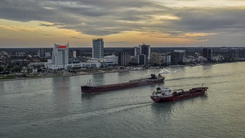 DXP002_192_0010 - Aerial stock photo of Oil tankers passing on the Detroit River near skyline of Windsor, Ontario, Canada, sunset