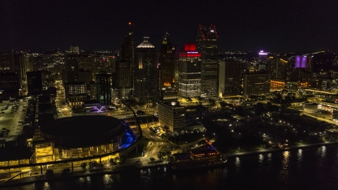 DXP002_199_0002 - Aerial stock photo of Towering skyscrapers and Hart Plaza at night, Downtown Detroit, Michigan