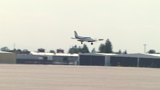 AF0001_000010 - Aerial stock footage of Tracking an airplane landing at a small airport, Central Valley, California