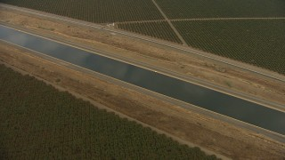 AF0001_000033 - Aerial stock footage of Pan across the California Aqueduct winding through farmland, Central Valley, California