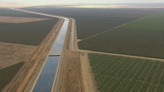 AF0001_000034 - Aerial stock footage of Tilt and fly over California Aqueduct winding through farmland, Central Valley, California