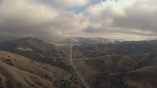 AF0001_000041 - HD stock footage aerial video follow Interstate 5 through Tejon Pass, California, with low clouds overhead