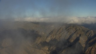 AF0001_000050 - HD stock footage aerial video fly through wisps of clouds to approach mountains in the Transverse Ranges, California