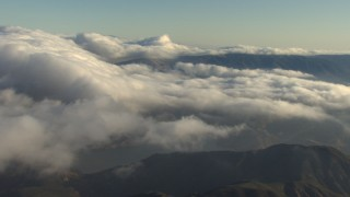 AF0001_000051 - Aerial stock footage of Flying over low clouds rolling over mountains, Transverse Ranges, California