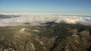 AF0001_000060 - Aerial stock footage of Approach low clouds behind wooded mountains, Transverse Ranges, California