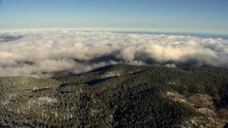AF0001_000061 - Aerial stock footage of Approach low clouds rolling toward wooded mountains, Transverse Ranges, California