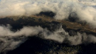 AF0001_000064 - Aerial stock footage of Bird's eye view of a small town below a layer of clouds in the Central Valley, California