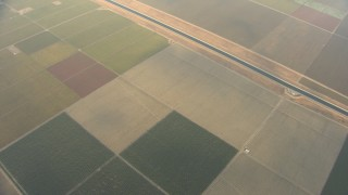 AF0001_000074 - HD stock footage aerial video of a bird's eye view of farmland, California Aqueduct, and light clouds, Central Valley, California
