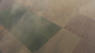 AF0001_000076 - HD stock footage aerial video of a bird's eye view flying over farmland and hazy clouds, Central Valley, California