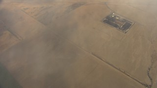 AF0001_000077 - Aerial stock footage of Bird's eye view of hazy clouds and farm fields in the Central Valley, California