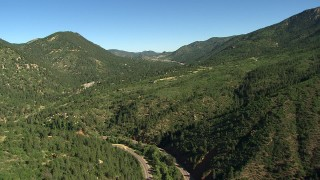 AF0001_000080 - HD stock footage aerial video follow a road through the Rocky Mountains, Colorado, and tilt to reveal a home