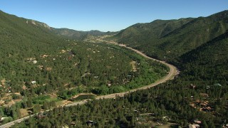 AF0001_000081 - HD stock footage aerial video tilt and fly over rural homes to approach a mountain highway in the Rocky Mountains, Colorado