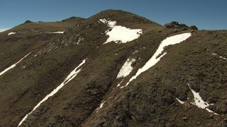 AF0001_000091 - HD stock footage aerial video flyby steep slopes with streaks and patches of white snow, Pikes Peak, Colorado