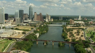AF0001_000107 - HD stock footage aerial video follow Lady Bird Lake over the 1st Street Bridge, tilt to cars crossing Congress Avenue Bridge, Downtown Austin, Texas