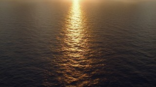 AF0001_000162 - HD stock footage aerial video of flying by reflection of rising sun off the water, Galveston Bay, Texas, sunrise