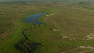 AF0001_000207 - HD stock footage aerial video of dirt roads and a pond in the countryside, Matagorda County, Texas
