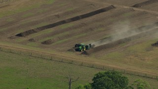 AF0001_000232 - HD stock footage aerial video approach a tractor working a farm field in Wharton County, Texas