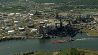 AF0001_000290 - Aerial stock footage of Flyby a barge sailing Buffalo Bayou past an oil refinery in Pasadena, Texas