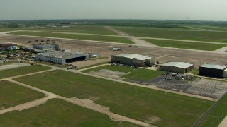 AF0001_000301 - Aerial stock footage of Flyby hangars with a view of helicopters and jet at Ellington Airport, Houston, Texas