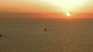 AF0001_000341 - Aerial stock footage of The rising sun and a pair of oil platforms in the Gulf of Mexico