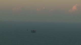 AF0001_000344 - HD stock footage aerial video of an oil rig surrounded by open sea at sunrise, Gulf of Mexico