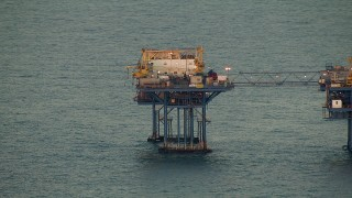 AF0001_000347 - Aerial stock footage of A large oil rig at sunrise in the Gulf of Mexico