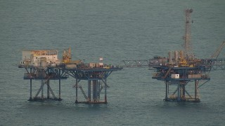 AF0001_000348 - Aerial stock footage of Part of a large oil derrick at sunrise in the Gulf of Mexico