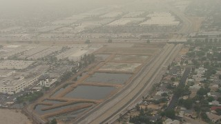 AF0001_000361 - HD stock footage aerial video flyby homes by Pacoima Wash and 210 Freeway, tilt to warehouses, San Fernando, California