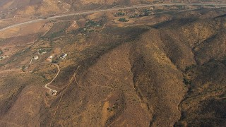 AF0001_000384 - HD stock footage aerial video tilt from dry hills to reveal homes and Highway 14, Agua Dulce, California