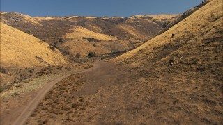 AF0001_000389 - HD stock footage aerial video of following a dirt road into the hills in Agua Dulce, California
