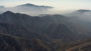 AF0001_000402 - HD stock footage aerial video fly over a mountain ridge to approach more mountains and a layer of clouds, Angeles National Forest, California