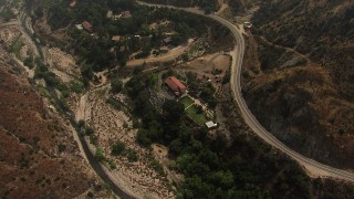 AF0001_000409 - HD stock footage aerial video of upscale homes beside a creek and mountain road in Rancho Tujunga, California