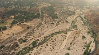 AF0001_000411 - HD stock footage aerial video of following Big Tujunga Canyon Road and creek through Rancho Tujunga, California