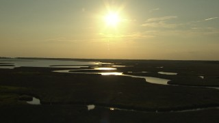 AF0001_000419 - HD stock footage aerial video flyby a river through wetlands with the setting sun overhead, Gulf Coast, Alabama