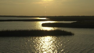 AF0001_000421 - HD stock footage aerial video fly over wetlands and a river reflecting the setting sun, Gulf Coast, Alabama, sunset
