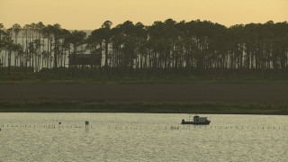 AF0001_000426 - HD stock footage aerial video of a boat in the bay near a lone house on stilts overlooking the water, Gulf Coast, Alabama, twilight