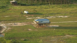 AF0001_000431 - HD stock footage aerial video zoom to a stilt house by a bay in Gulf Coast, Alabama, sunset