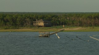 AF0001_000432 - HD stock footage aerial video of a stilt house by docks in the shore of the bay on the Gulf Coast, Alabama, sunset