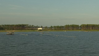 AF0001_000433 - HD stock footage aerial video flyby stilt houses and docks on the shore of a bay in the Gulf Coast, Alabama, sunset