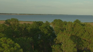 AF0001_000434 - HD stock footage aerial video of flying over trees to reveal a bay at sunset, Gulf Coast, Alabama