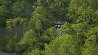 AF0001_000440 - HD stock footage aerial video of a small bridge spanning a river in the forest at sunset, Gulf Coast, Alabama